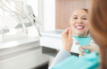 middle-aged woman looking at her teeth in the mirror