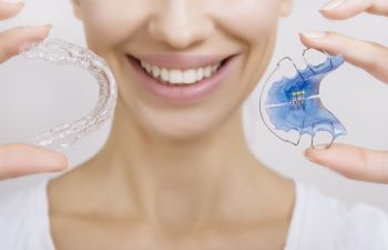 woman holding Invisalign and traditional braces